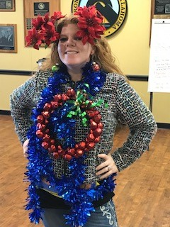 Chelsea Choate rocks the Ugly Sweater Contest in a multicolored sweater adorned with a tinsel necklace and jingle bell wreath pendant.  The poinsettia bunches above her ears add the finishing touch.