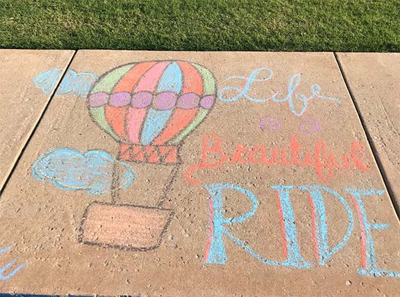 For the Chalk Art Contest artist, Jordan Ellis, draws a baloon with the text